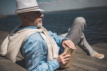 senior man lying with book on quay