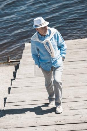 fashionable senior man walking on riverside