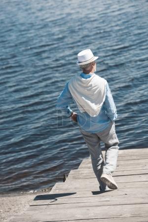 casual senior man walking on riverside