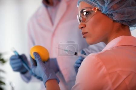 Female scientist holding lemon