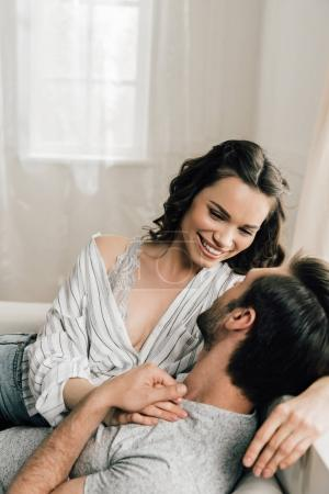 Photo for Happy young couple hugging and smiling each other at home - Royalty Free Image