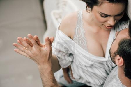 Photo pour Recadrée tir de passionnés jeune couple main dans la main préliminaires à la maison - image libre de droit