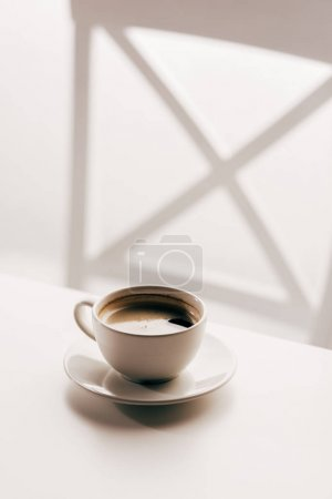Photo for Close-up view of fresh black coffee in cup on white wooden table - Royalty Free Image