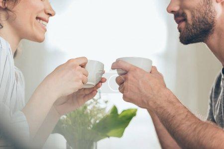 Photo for Cropped shot of happy young couple drinking coffee together at home - Royalty Free Image