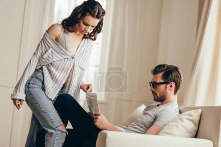 Photo for Sensual young woman touching bearded man in eyeglasses sitting on sofa and reading newspaper - Royalty Free Image
