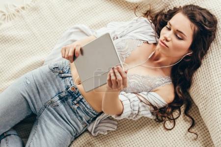 Photo pour Jeune femme séduisante portant des écouteurs mentant et utilisant une tablette numérique - image libre de droit