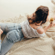 High angle view of young woman lying and holding c...