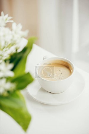 Photo for Close up of cup of coffee with bouquet of flowers on white tabletop - Royalty Free Image