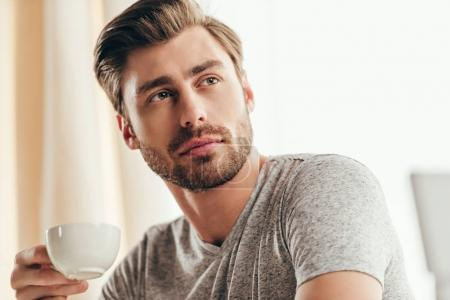Photo for Portrait of young handsome man drinking coffee at home - Royalty Free Image