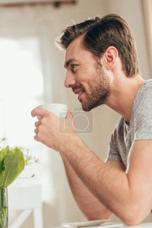 Handsome man drinking coffee at home