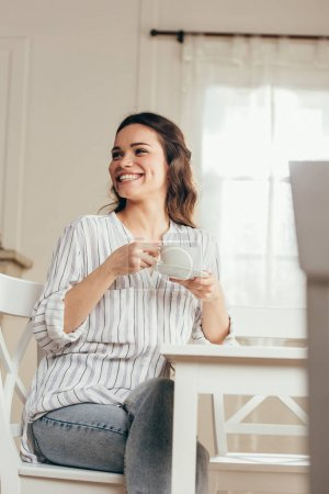 Smiling girl drinking coffee at home