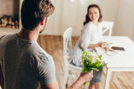 Photo pour Homme présentant bouquet de fleurs à sa petite amie souriante à la maison - image libre de droit