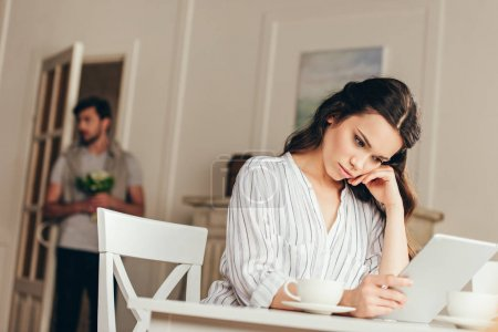 Photo for Pensive young woman sitting at table and using digital tablet at home - Royalty Free Image