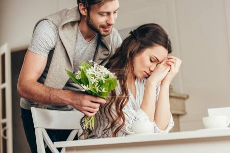 man presenting flowers to girlfriend at home