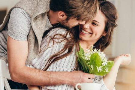 Photo for Young casual couple embracing with bouquet of flowers at home - Royalty Free Image