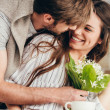 Young casual couple embracing with bouquet of flow...