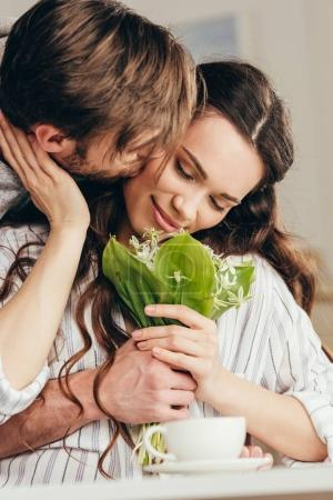 couple embracing and kissing with bouquet of flowers