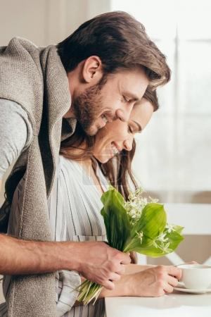man embracing girlfriend with bouquet of flowers
