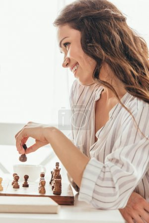 Smiling woman moving chess figure