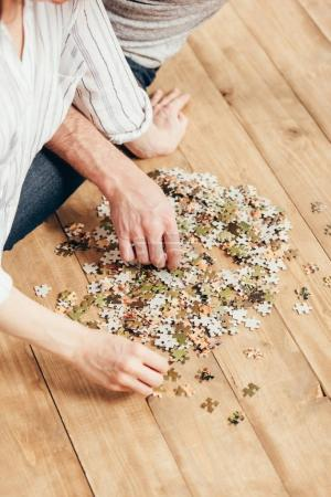 couple collecting puzzle on wooden floor