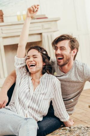 Photo for Young couple laughing and fooling around with puzzles while sitting at home - Royalty Free Image