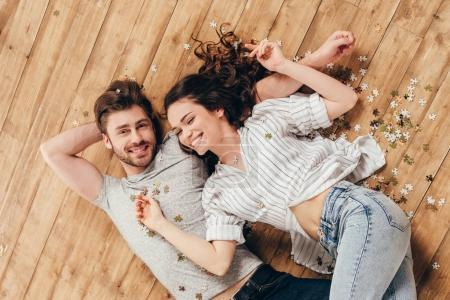 Young smiling couple lying on floor