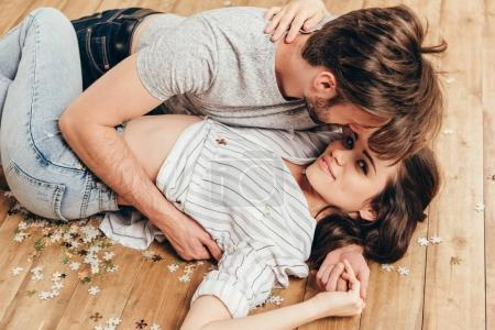 Photo for Young sensual couple hugging in foreplay while lying on the floor at home - Royalty Free Image