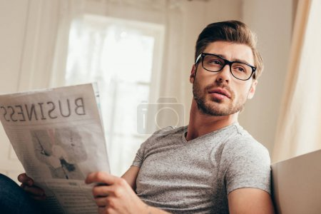 young man reading newspaper at home