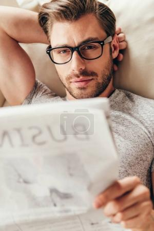 young man in glasses reading newspaper