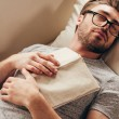 Portrait of young man sleeping with book on sofa a...