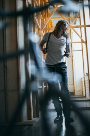 Photo for Full length view of handsome young man with long hair walking and looking away - Royalty Free Image
