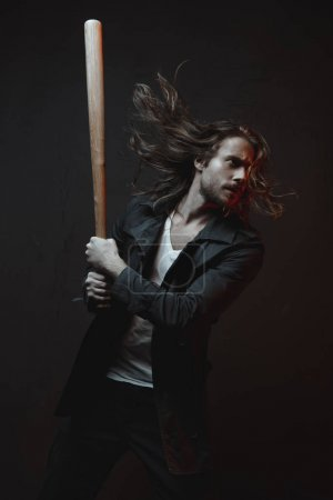 Photo for Young long haired man holding baseball bat ready to hit in darkness - Royalty Free Image