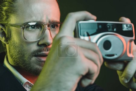 man taking photo on compact camera