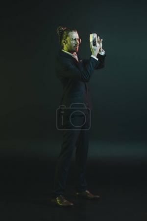 Photo pour Jeune homme élégant en costume tenant la photo sur l'appareil photo compact - image libre de droit