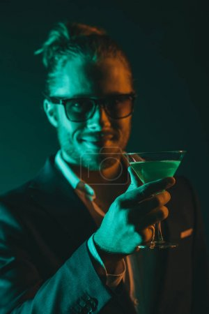 smiling man holding glass with cocktail