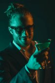 stylish man holding glass with cocktail