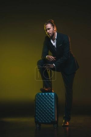 pensive man in suit leaning on suitcase