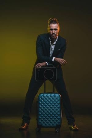 Photo pour Jeune homme en smoking appuyé sur la valise et regardant la caméra - image libre de droit