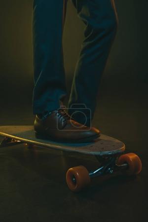 Man in formal wear riding on skateboard