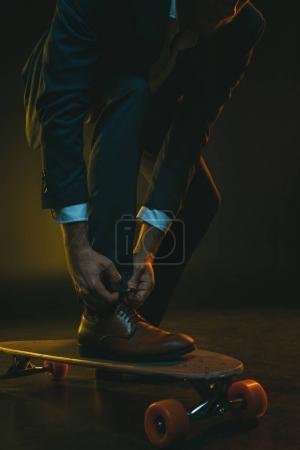 fashionable man tying shoelaces on skateboard