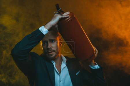 man in suit holding fire extinguisher