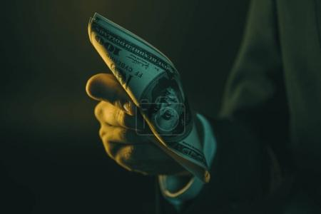 man holding us dollar banknotes