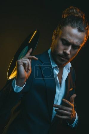 Man in tuxedo holding vinyl record