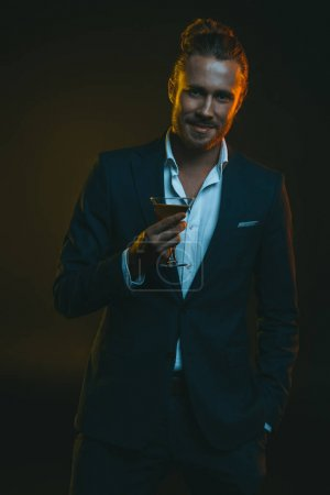 Man in tuxedo holding glass with cocktail