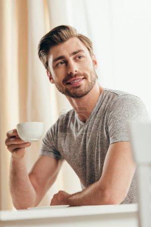 Photo pour Souriant jeune homme tenant tasse de café et regardant loin à la maison - image libre de droit
