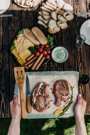 Photo for Top view of man holding wooden board with raw ribeye steaks decorated by spices and rosemary - Royalty Free Image