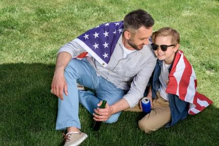 Photo for Father and son sitting on grass with us flag and holding beer and soda, America's Independence Day concept - Royalty Free Image