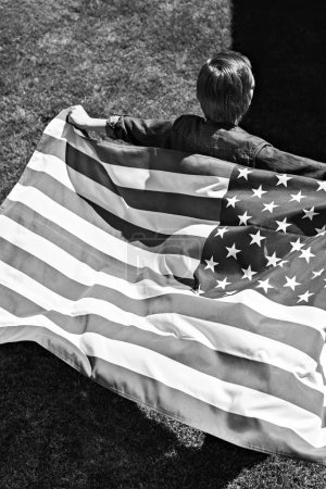 Photo for Little boy running with american flag, America's Independence Day concept, black and white - Royalty Free Image