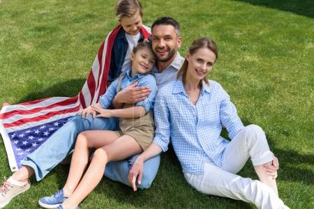 Photo for Happy parents and children relaxing on grass with american flag, celebrating 4th july - Independence Day - Royalty Free Image