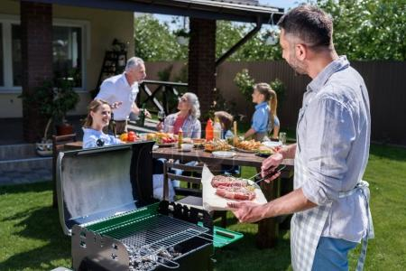 Photo for Bearded man in apron grilling meat and happy family sitting at table outdoors - Royalty Free Image